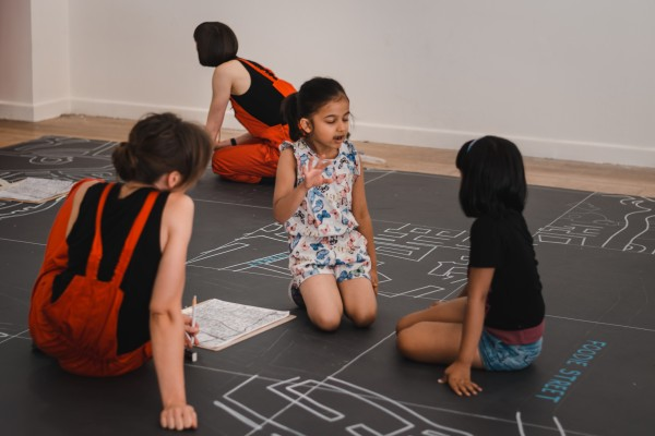 2 girls sit on a large map drawn on the floor, talking animatedly
